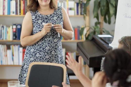 Naemi steht lächelnd vor Regal und neben Flipchart mit Stift in der Hand, vorne gestikulieren Personen sitzend